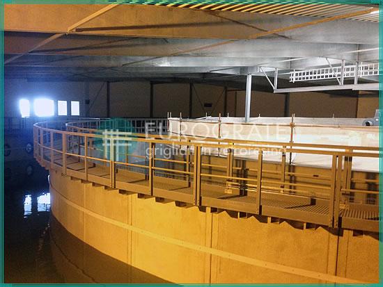 Laufstege mit Gitterrosten und Sicherheitsgeländern in einem Becken in der Fischereiindustrie
